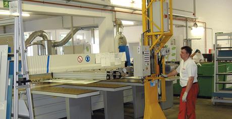 Regalbediengerät mit Vakuumsauger, das Platten auf einer Bearbeitungsmaschine ablegt